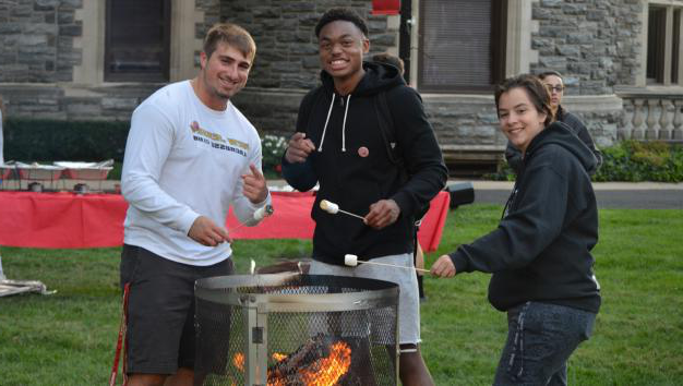 Honors students having a bonfire in front of Grey Towers Castle