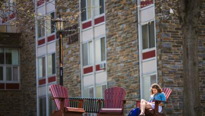 Arcadia student sitting in chairs outside Brubaker Hall