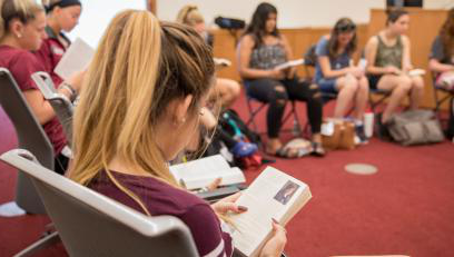 Group of students reading common read book in group discussion session